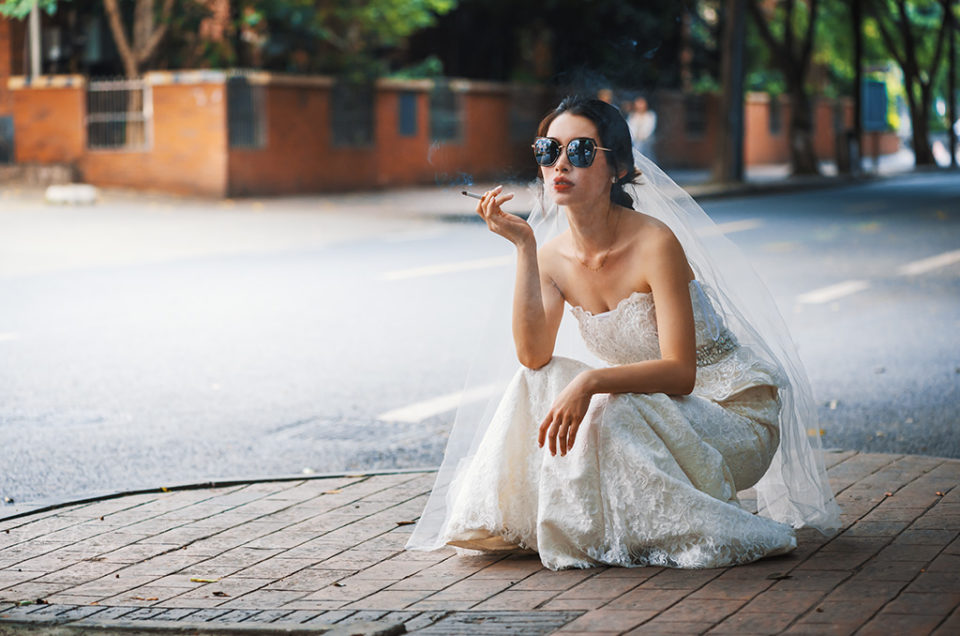 Young chinese bride with sunglasses squat in the street and smoking a cigarette in Chengdu, Sichuan province, China