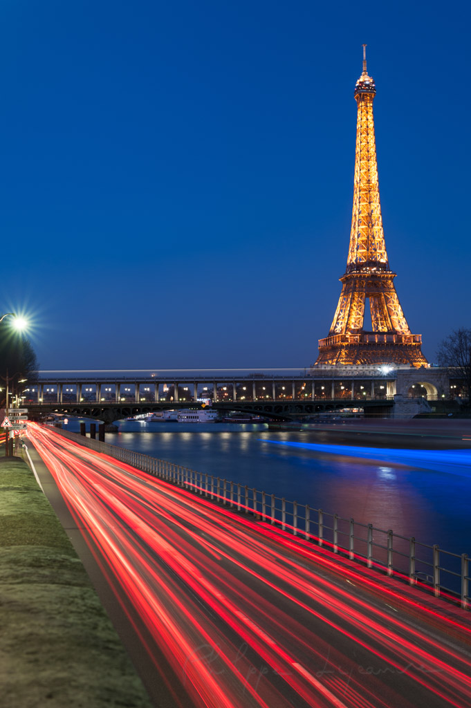 Paris - Eiffel Tower and Bir Hakeim bridge at blue hour with red traffic trails