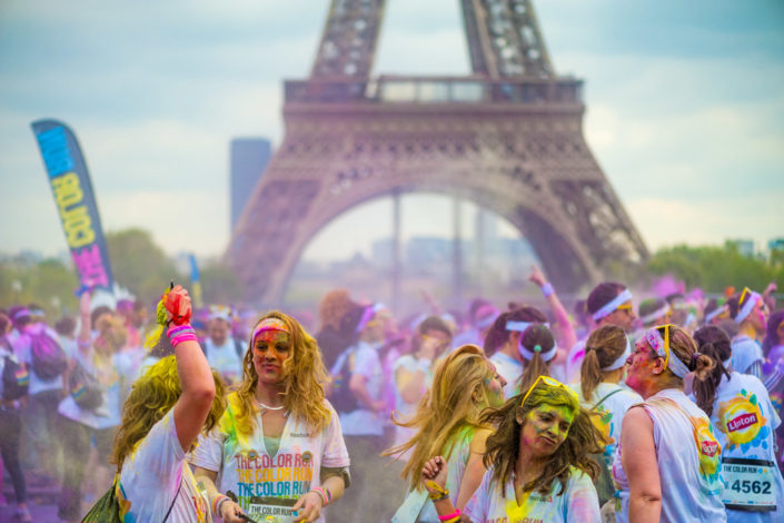 Paris, France - April 13, 2014: People enjoying the party with colorful powder under the Eiffel Tower after the color run race.