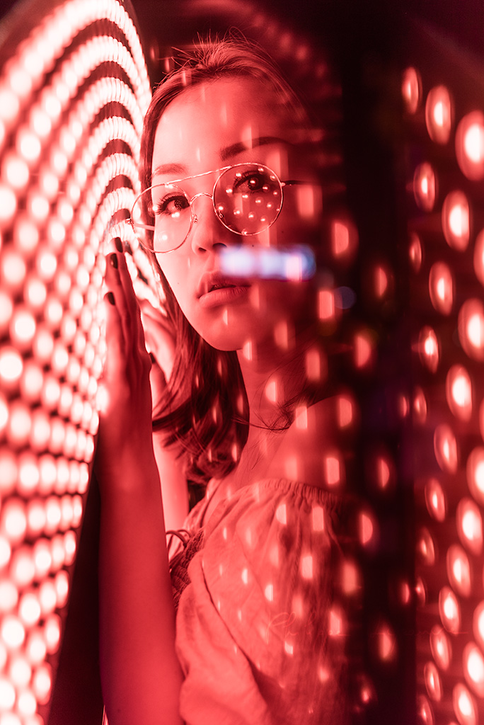 Young woman neon portrait at night with red lights in Chengdu, Sichuan province, China / Model: Fanny
