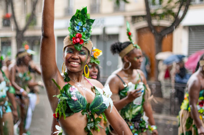 Young women dancing under the rain at the Paris tropical carnival, France