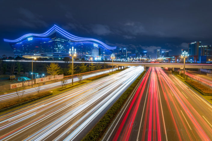 Traffic light trails on Tianfu avenue at night with illuminated New Century Global Center in the background, Chengdu, Sichuan province, China