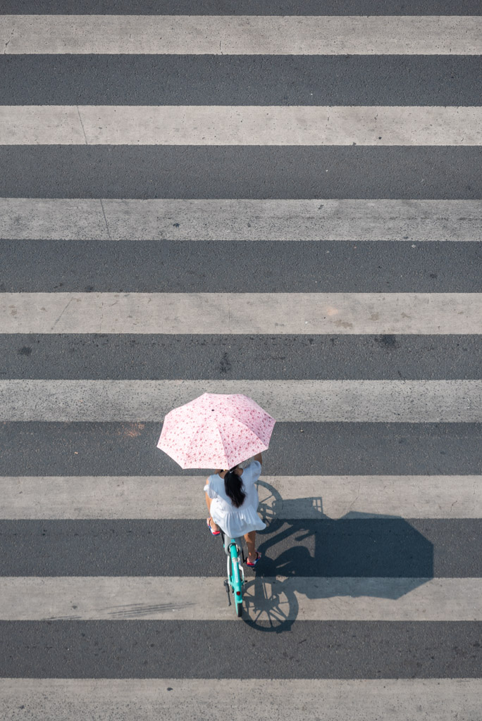 Chinese girl on a bike crossing the road aerial view in Chengdu, Sichuan province, China