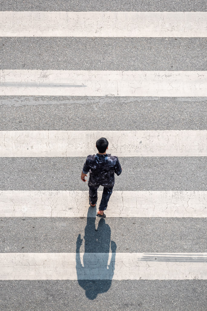 Young man crossing the street aerial view in Chengdu, Sichuan province, China