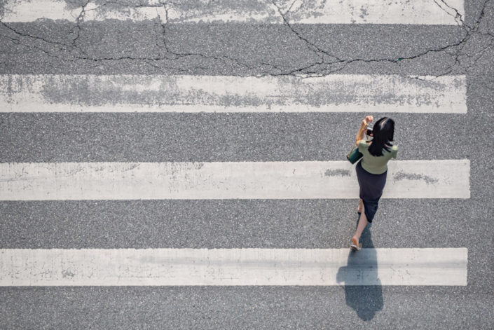 Young woman crossing the street aerial view in Chengdu, Sichuan province, China