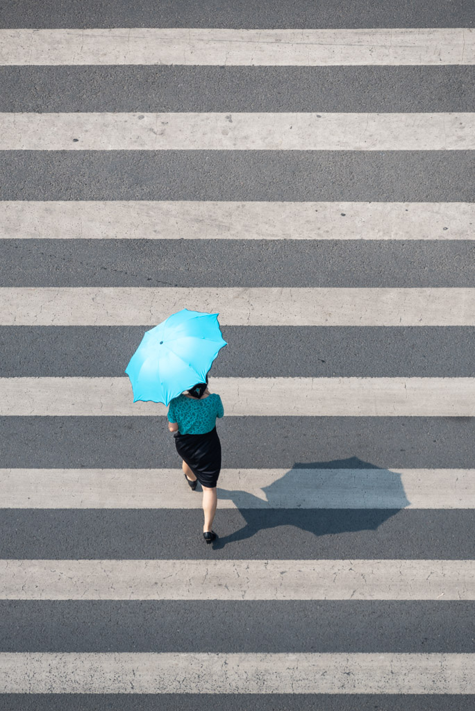 Woman with an umbrella crossing the street aerial view in Chengdu, Sichuan province, China
