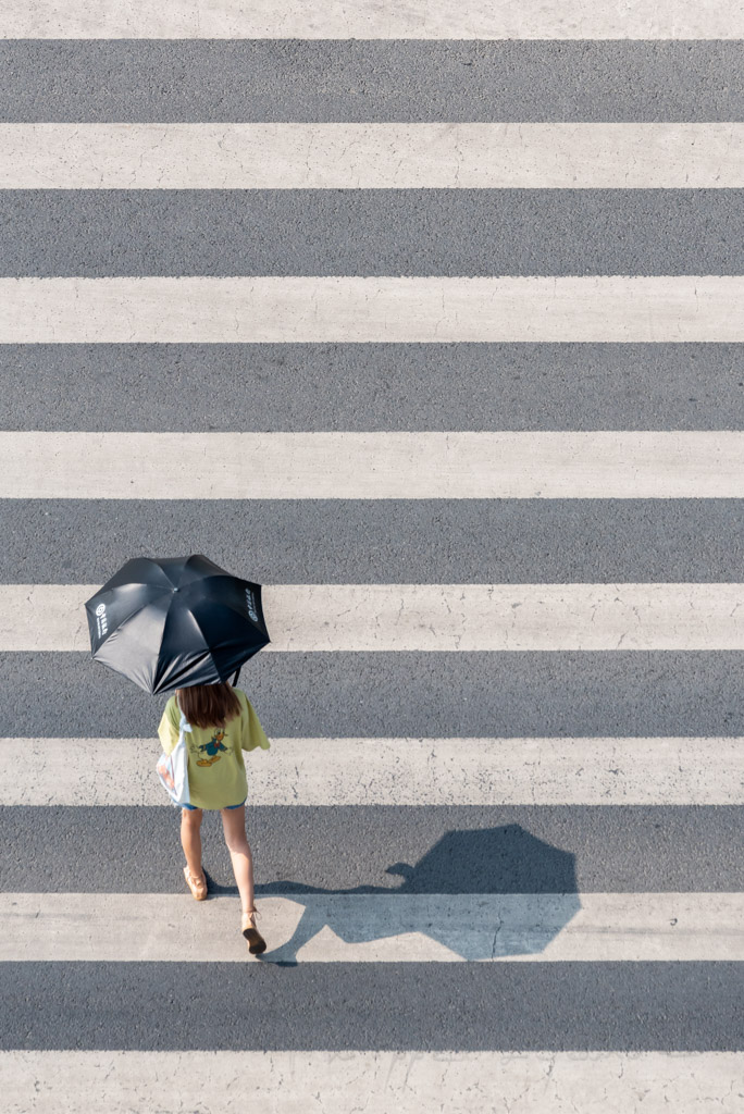 Young woman with an umbrella crossing the street aerial view in Chengdu, Sichuan province, China