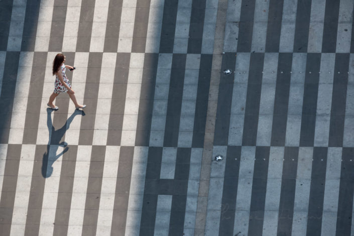 Chinese woman walking on zebras markings aerial view in Chengdu, Sichuan province, China