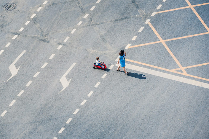 Woman with child crossing the road in Chengdu, Sichuan province, China