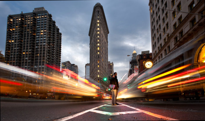 Couple crossing the street in front of the Flatiron building, New York City, USA