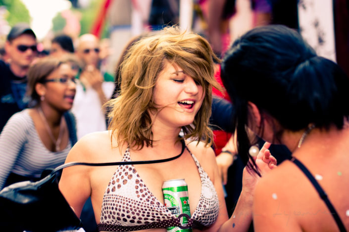 Young woman dancing with a beer at the Paris pride, France
