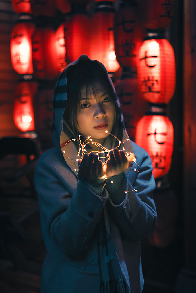 Young woman holding lights portrait at night with chinese lanterns in the background in Chengdu, Sichuan province, China / Model: @Ozozzzz