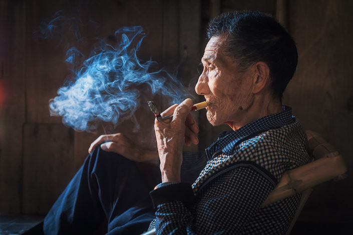 Portrait of an old chinese man smoking in an ancient tearoom in Chengdu, Sichuan Province, China