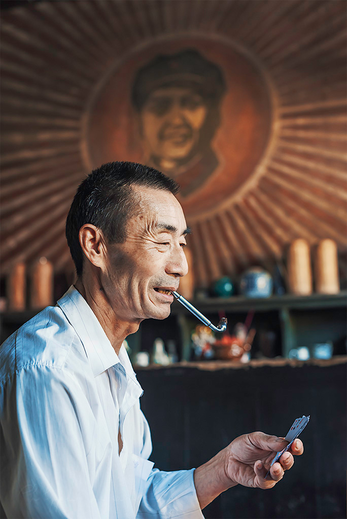 Portrait of an old chinese man playing cards and smoking in an ancient tearoom, Chengdu, Sichuan province, China