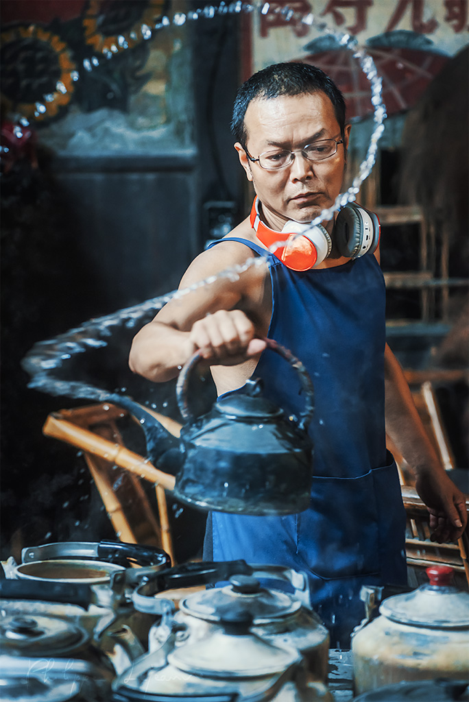 Chinese man with headphones playing with boiling water pouring from an old teapot, Chengdu, Sichuan province, China