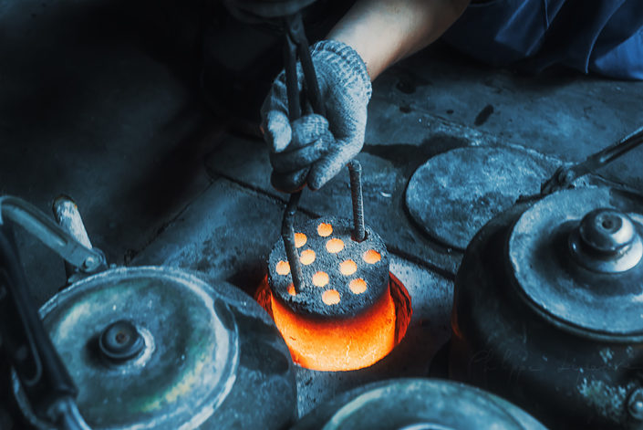 Hand holding hot harcoal from an ancient oven, Chengdu, Sichuan province, China