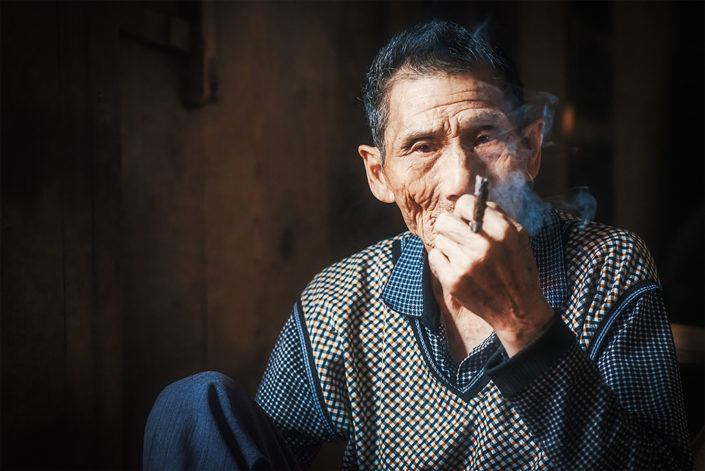 Portrait of an old chinese man smoking in an ancient tearoom, Chengdu, Sichuan province, China