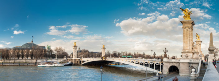 Panorama of Alexander III bridge in Paris with blue sky and white clouds.