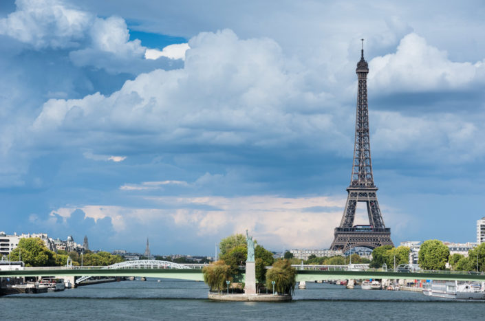 Paris - Eiffel tower, statue of liberty and river Seine with clouds on the background