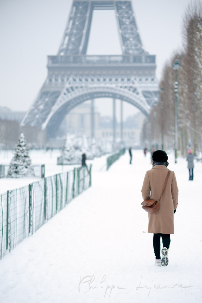 Woman walking on the snow with the Eiffel tower in the backgrund in Paris