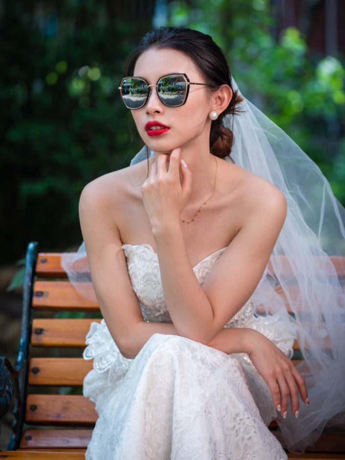 Young chinese bride with sunglasses sitting on a bench in Chengdu, Sichuan province, China
