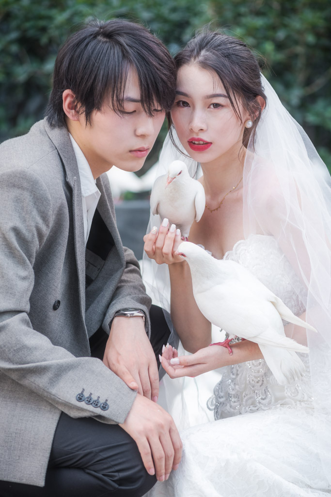 Young married couple with white doves in Chengdu, Sichuan province, China