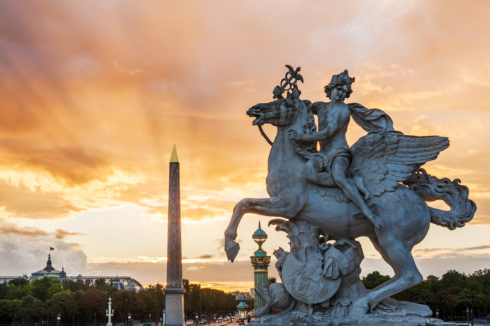 Statue Of Perseus And Obelisk on Place De La Concorde In Paris at sunset with light rays in the clouds
