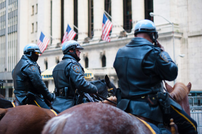 Three policemen on horses in front of the New York Stock Exchange building, New York City, USA