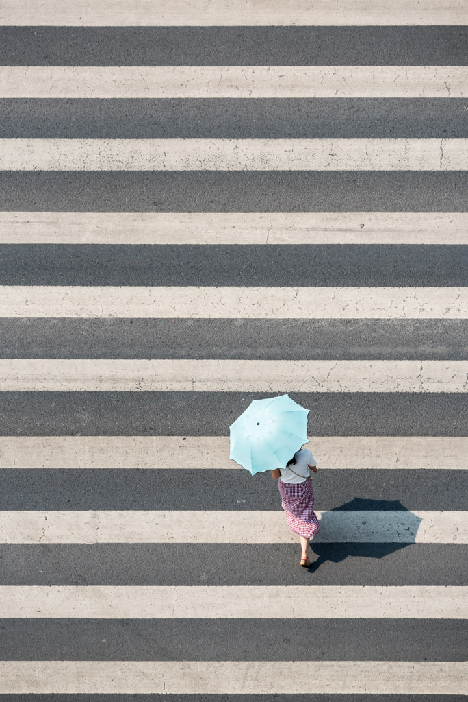 Woman with an umbrella crossing a street in Chengdu, Sichuan province, China