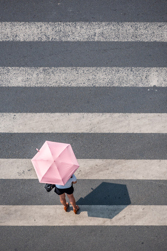 Woman with an umbrella crossing the street in Chengdu, Sichuan province, China