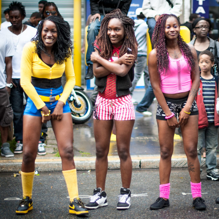 Three young women with colorful outfit watching the tropical carnival in Paris, France