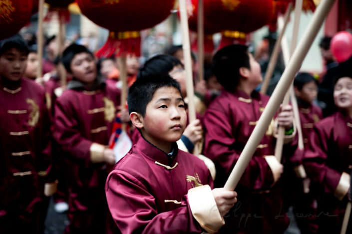 Young boy holding a chinese lanter at the Chinese new year parade in Paris, France