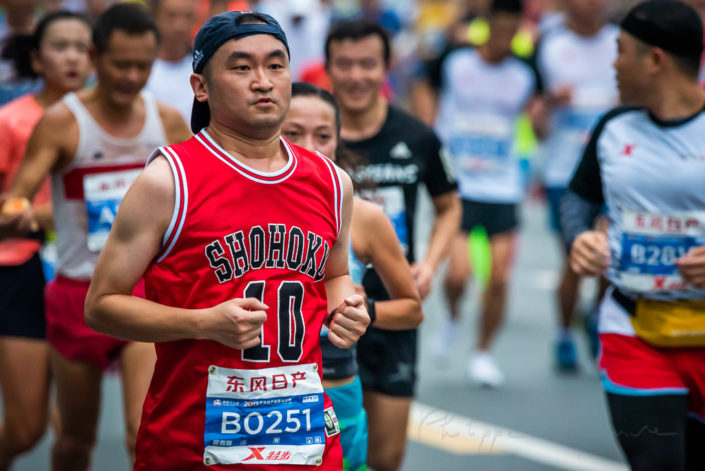 Chengdu, Sichuan province, China - Oct 27, 2019 : Young man running at the Chengdu marathon with a red basketball T-Shirt
