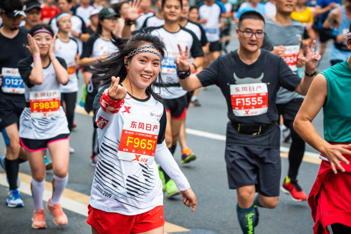 Chengdu, Sichuan province, China - Oct 27, 2019 : Young woman running at the Chengdu marathon and doing the chinese love sign