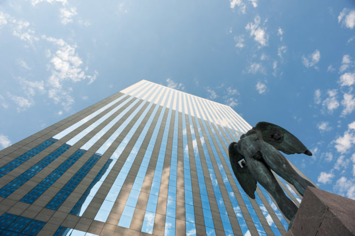 "Low angle view of an angel statue and a building against the blue sky in the business district of La Defense, Paris - France. The statue is from Igor Mitoraj and is called ""Ikaria"""