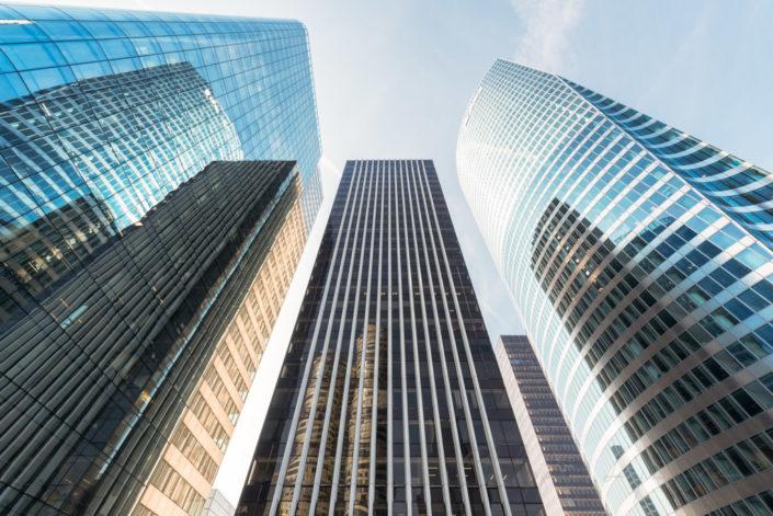 Modern glass skyscrapers against blue sky in La Defense business district, Paris, France