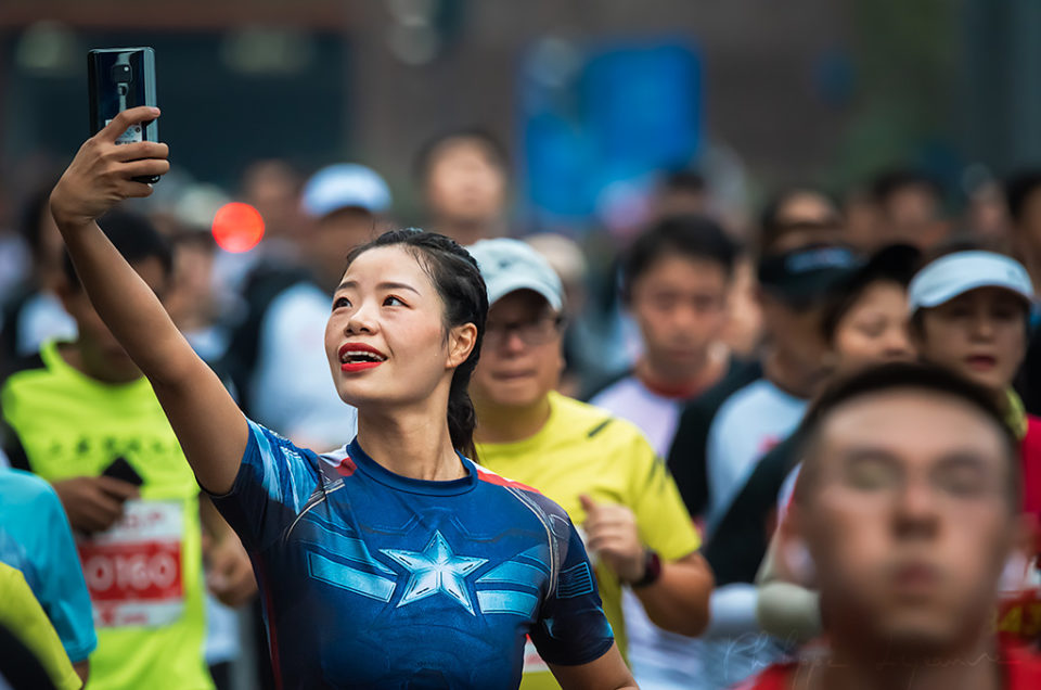 Chengdu, Sichuan province, China - Oct 27, 2019 : Young woman with a captain america T-Shirt taking a selfie at the Chengdu Marathon