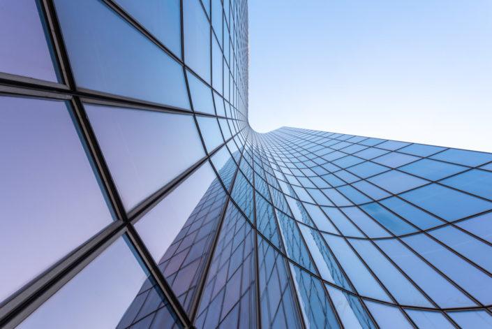 Manhattan tower curved building against blue sky in La Defense business district, Paris, France