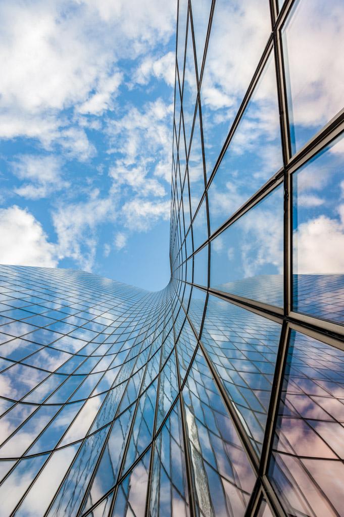Manhattan tower curved glass building against blue sky in La Defense business district, Paris, France