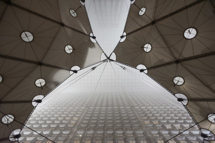 Low angle vertical view of the Grande Arche de la Defense in the mist, Paris, France