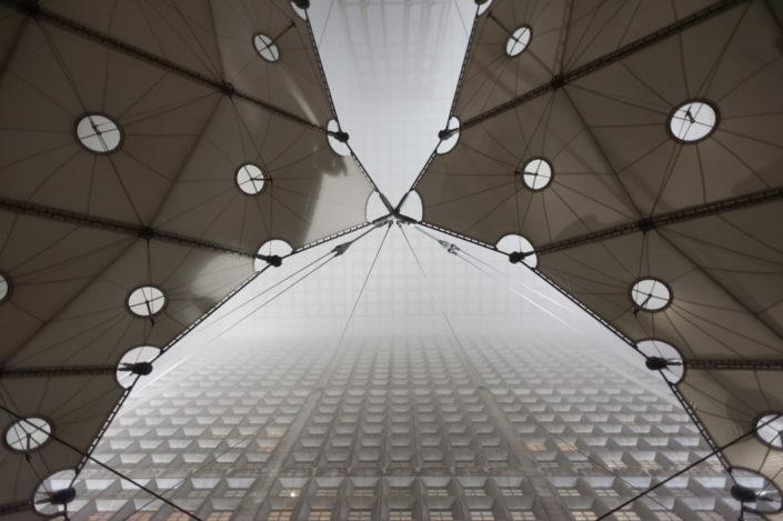 Low angle vertical view of the Grande Arche de la Defense in the mist, Paris, France