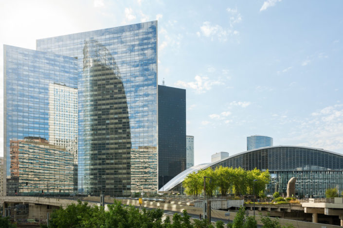 La Defense business district buildings reflections against blue sky, Paris, France