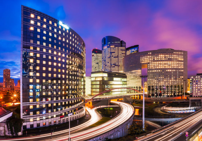La Defense business district at night with lights in the buildings and car light trails on the roads, Paris, France
