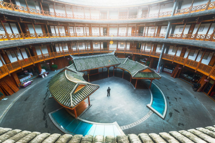Luodai, Sichuan Province, China : Man standing in a Hakka traditional round house with sunlight coming from the roof.