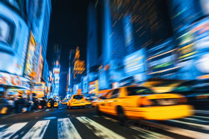 New York city street at night with yellow taxi in the foreground - motion blur radial effect, USA