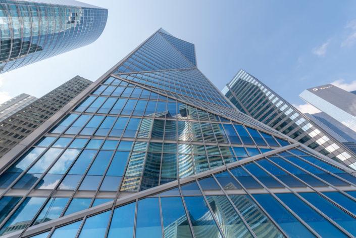Carpe diem tower against blue sky in la Defense business district in Paris, France