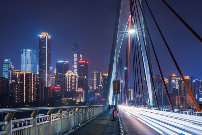 Chongqing illuminated skyline behind cable bridge at night, China