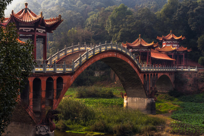 Ancient traditional chinese bridge in the fog in Leshan giant buddha touristic area - Chengdu, Sichuan Province, China