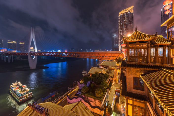 Hongya cave high angle view at night with Qiansimen bridge and an illuminated boat in the river, Chongqing, China