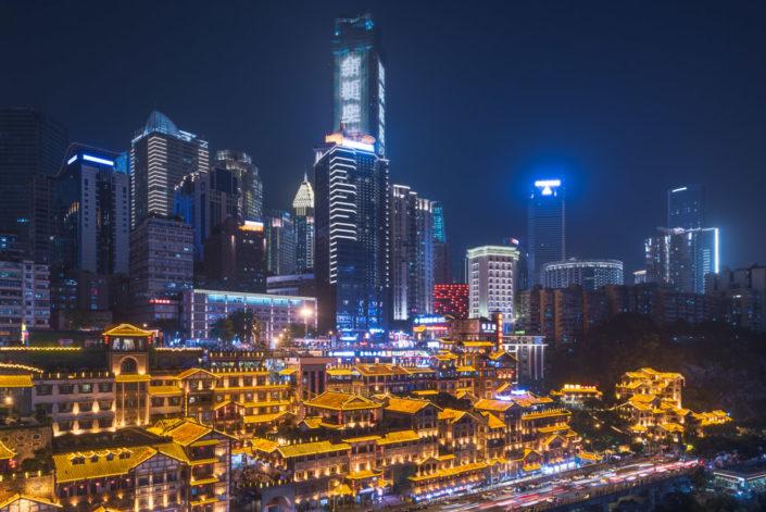 Skyscrapers and Hongya cave illuminated at night in Chongqing, China
